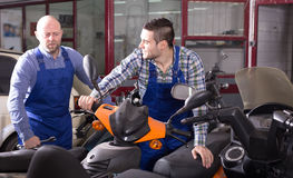 Car mechanics inspect motor bikes Royalty Free Stock Image