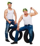 Car mechanics isolated. Dancers dressed as car mechanics with tools and tire, isolated against white background Stock Photos