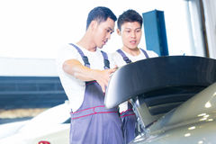 Car mechanics looking under hood of sports car Stock Image