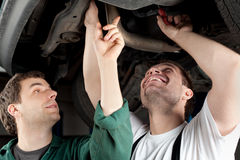 Car Mechanics repairing car Royalty Free Stock Image