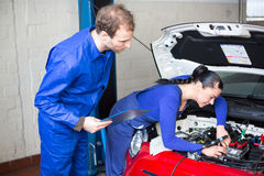 Car mechanics repairing the electrics. Car mechanics repairing car electrics and other parts of the motor royalty free stock image