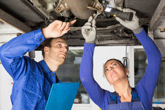 Mechanics repairing a car on hydraulic ramp Royalty Free Stock Photo