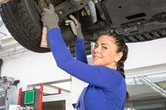 Mechanics repairing a car on hydraulic ramp Stock Images