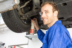 Mechanics repairing a car on hydraulic ramp Royalty Free Stock Image