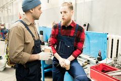 Car Mechanics Talking On Break. Young bearded auto technician in work uniform chatting with his male colleague during coffee break in service garage Stock Photo