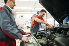 Car mechanics working at automotive service center. Together royalty free stock photo