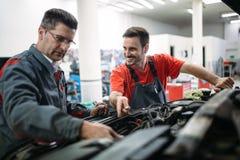 Car mechanics working at automotive service center. Together stock photos