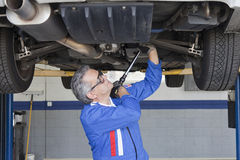 Car mechanics working below a car using a monkey wrench Royalty Free Stock Photography