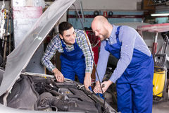 Car mechanics  working at carshop Stock Images