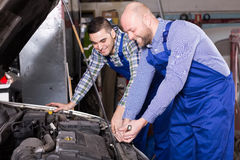 Car mechanics  working at carshop. Smiling american car mechanics  working at carshop Royalty Free Stock Image