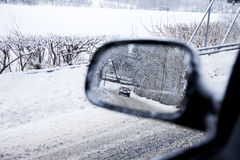 Car in a Mirror. Drivers view of a car in the mirror at a road in wintertime Royalty Free Stock Photography