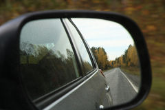Car mirror. Reflected in speeding car mirror on russia freeway highway; freedom travel concept; autumnal color trees and road Stock Photography