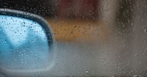 Car mirror and a transparent window with raindrops. Abstract, blurred background, copy space. Stock Photos