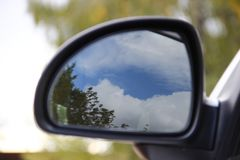 Car mirror on the green background. Blue sky, mirroring, reflection. Sunny day royalty free stock image