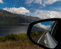 Car mirror reflection on road by the lake royalty free stock photography