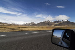 Car mirror on a the ring road in Iceland. Horizontal photo of a car mirror on the side of a paved road in Iceland with mountains and blue sky in the background Royalty Free Stock Photography