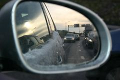 Car mirror with Snow. Car mirror in which you can see the snow on the car and other cars on the road stock photography