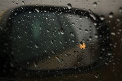 A car mirror through the window spattered with rain stock photos