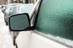 Car mirror and windows are covered with ice after freezing rain. Royalty Free Stock Image