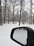 Car mirror with winter woods reflection royalty free stock image