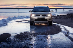 Car Mitsubishi Outlander stay on ice coast at winter sunset Stock Photos