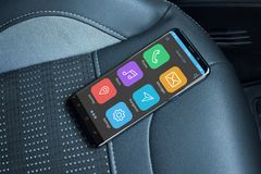 Car mobile app on modern mobile phone with flat edges. Smart phone on leather seat royalty free stock image