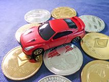 car model lay on crypto coin on blue cloth. Virtual cryptocurren Stock Image