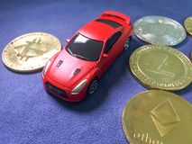 car model lay on crypto coin on blue cloth. Virtual cryptocurren Stock Photos