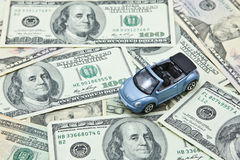 Car model on pile of US dollar banknotes Stock Photo
