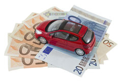 Car and money. Red little car on euro banknotes isolated on white background. Saving money for a car concept Royalty Free Stock Photo