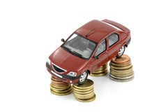 Car and money. Small car standing on coins against white background stock image