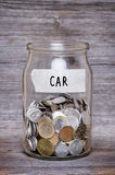 Car, money jar with coins on wood table Stock Images