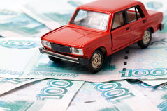 Car and money. Toy car on the background of banknotes Stock Photos