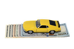 Car and money. Yellow classic sport car over bundle of money Royalty Free Stock Image