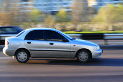 Car in motion. Silver car in motion on the road. Profile Stock Photos