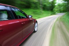 Car in Motion. Red Moving along a Country Road Royalty Free Stock Photo