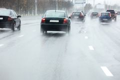Car in motion spraying water from the wheels during rainy weathe Stock Image