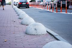 Car or motor vehicle stop security barriers or hemispheres bollards. Concrete structures to prevent parking on the sidewalks are p. Laced at the edge of the Royalty Free Stock Photo