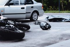Car and motorbike crash. Site with a helmet lying in the middle of the street Stock Photo