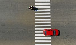 Car and motorcycle crossing a pedestrian crosswalk zebra on a highway.  stock images