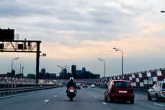 Car and motorcycle on the highway-evening. Stock Image