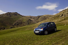 Car on a mountain slope. Blue car on a mountain slope with green grass Royalty Free Stock Photos