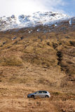 Car in the Mountains. A silver car parked beneath a large mountain in Scotland royalty free stock image
