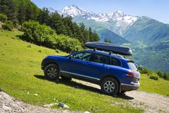 Car in mountains. Car is an off-road car in mountain on clear, sunny summer day. Travel by car through the wild. Trip to the mountains by car. Amazing royalty free stock images
