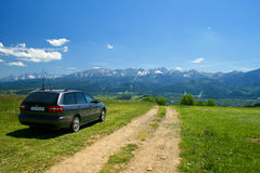 Car in mountains scenery. Perfect high mountains journey with family wagon car. Great idea for summer vacation relax Stock Photography