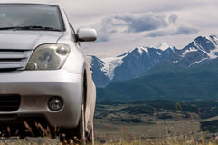 Car mountains snowy peaks. Car in a picturesque location with view the hills and mountains, covered by forests and snow-capped peaks on the horizon stock image