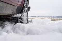 Car with mounted snow chains in wintry environment.  Royalty Free Stock Photography