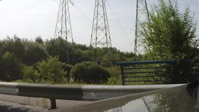 Car move under power lines. The car moves along the road under the power line. Side view stock footage