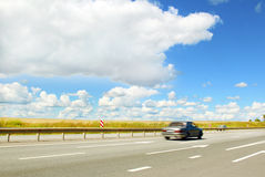 The car moves. The car moves along an asphalt road in cloudy weather in the summer royalty free stock images
