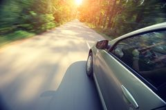 Automobile moves at fast speed at sunrise. The car moves at fast speed at sunrise in the forest Royalty Free Stock Photo